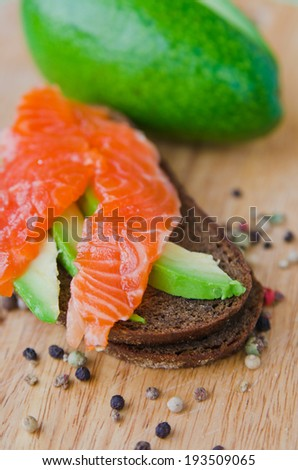 black bread with red fish and avocado - stock photo