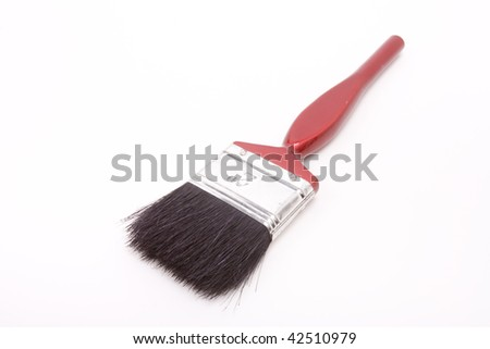 Black bristled paint brush from low viewpoint against white background.