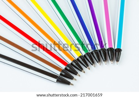 Black, brown, red, orange, yellow, green, dark blue, purple, pink and light blue ballpoint pens on white background - stock photo