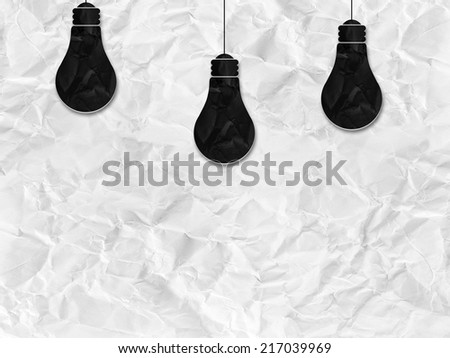 black bulb silhouette on white crumpled paper - stock photo