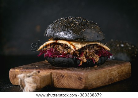 Black burger with beef stews, cheese, red cabbage and balsamic sauce served on small wooden chopping board over wooden table with black background.