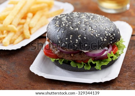 Black burger with French fries and beer - stock photo