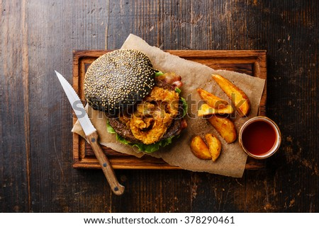 Black burger with sesame seed bun, meat, bacon, onion fries rings and potato wedges on dark wooden background - stock photo