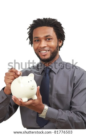 Black business man putting a coin in his piggy bank - stock photo
