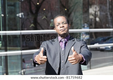 Black business man with classes showing thumbs up outdoor - stock photo