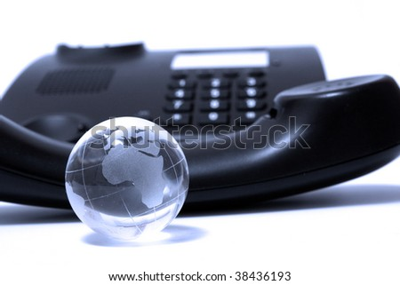 Black business phone and glass globe in blue light - stock photo