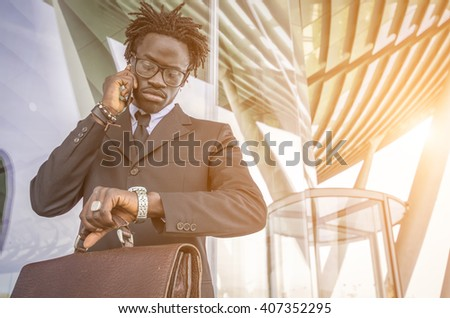 Black businessman delayed checking the time in the watch while he is making a telephone call with his mobile phone - stock photo