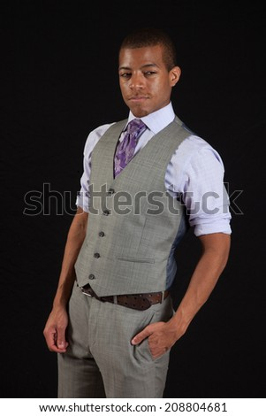 Black businessman in vest and tie with his hand in his pocket, looking thoughtful and serious