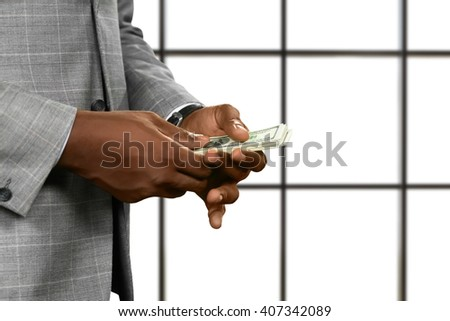 Black businessman's hands holding money. American dollars on white background. It's never enough. Always chasing success. - stock photo