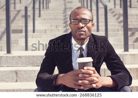 black businessman sitting with coffee during a lunch - stock photo