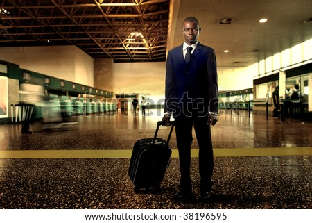 Black businessman with suitcase at the airport - stock photo