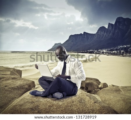 black businessman working on the beach with laptop