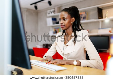 Black businesswoman using computer in office and typing on keyboard - stock photo
