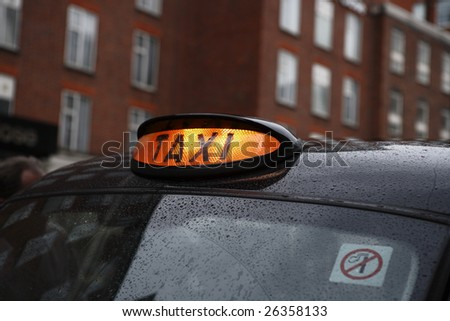 Black cab taxi in London under some rainy weather. - stock photo