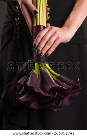 Black Calla Lilies bouquet in the hand of a woman - stock photo