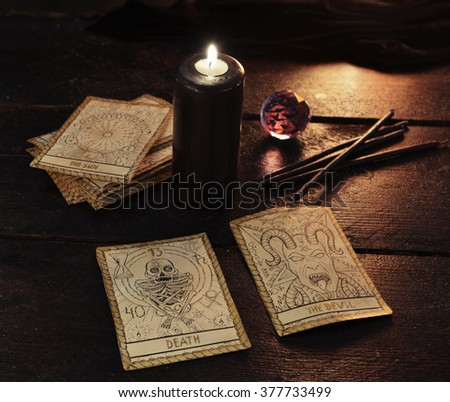 Black candle with the tarot cards and crystal ball. Halloween and magic still life, fortune telling seance or black magic ritual with mysterious occult and esoteric symbols, divination rite  - stock photo