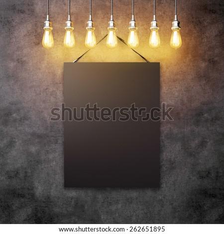 Black canvas hanging under decorative vintage light bulbs  - stock photo