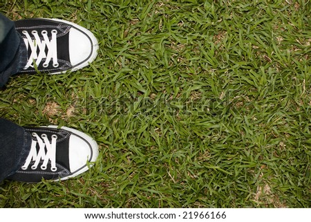 Black canvas sneakers on grass, copy space on the right - stock photo