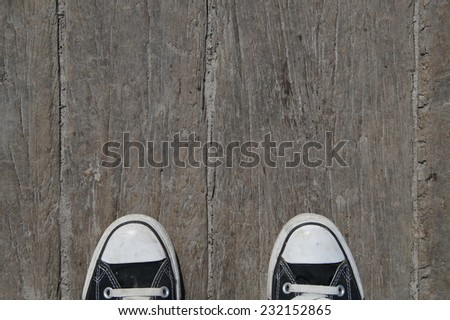 Black canvas teenager baseball shoes on wooden background  - stock photo