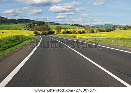 Black car arriving down the empty asphalt road through the yellow blossoming rape field in the countryside. In the background of forested mountains.