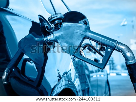 Black car at gas station being filled with fuel  - stock photo
