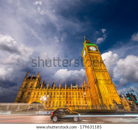 Black car driving past the Houses of Parliament and Big Ben - London. - stock photo