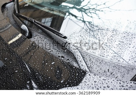 Black car hood fragment and windshield wipers with raindrops on it, closeup photo with selective focus and shallow DOF - stock photo