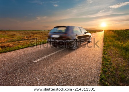 Black car in motion blur on the road towards the setting sun - stock photo