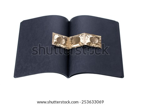 black cardboard notebook with golden condoms on a white background - stock photo