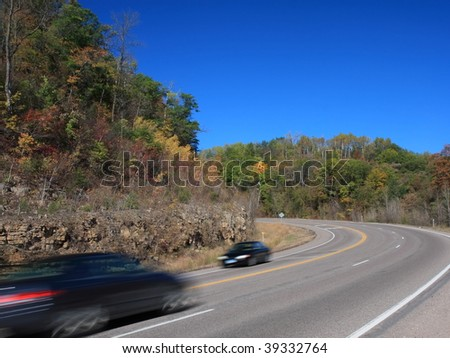 Black cars on the road in Minnesota at autumn season