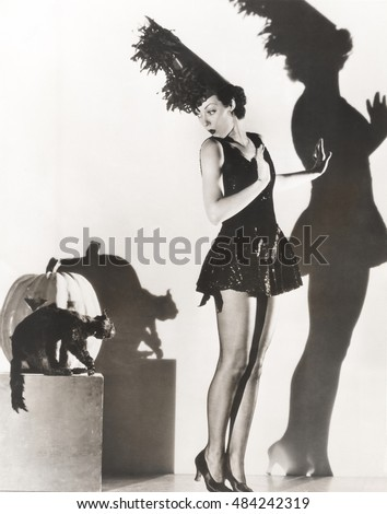 Black cat giving woman in costume the heebie-jeebies