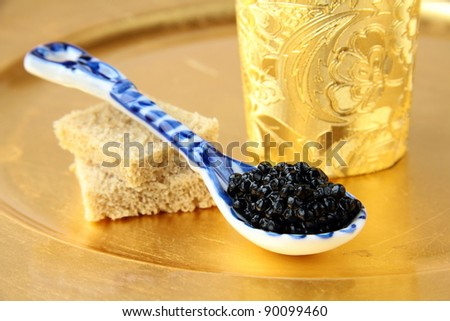 Black caviar in spoon on gold background - stock photo