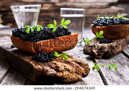 Black caviar on a piece of dark bread on a wooden surface in rustic style - stock photo