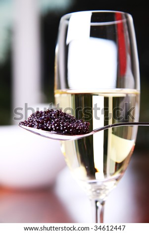 Black caviar on a spoon next to a glass of champagne