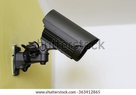 black CCTV camera on the yellow wall - stock photo