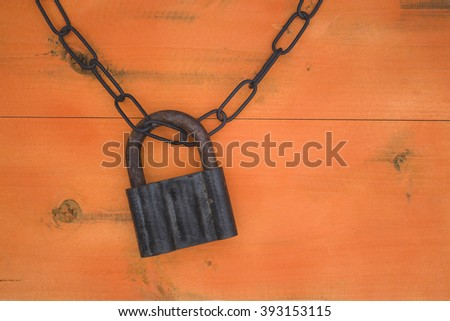 black chain and padlock on the wooden surface orange