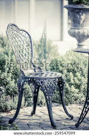 Black chair in English garden. vintage style - stock photo