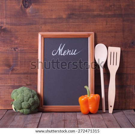 Black chalkboard for menu and fresh vegetables over wooden background. Diet food concept. - stock photo