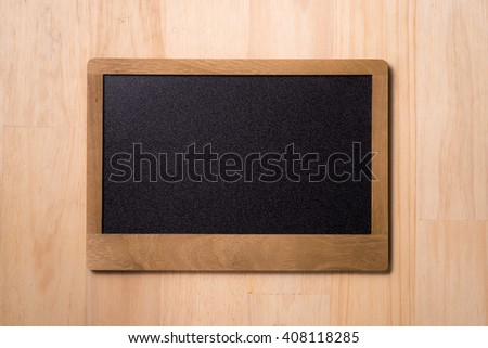 Black chalkboard over wooden table. Blank chalkboard with wood frame, erased and ready for your message - stock photo