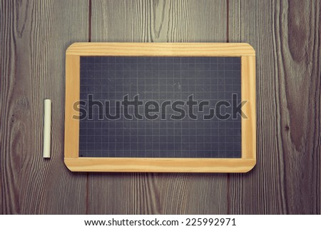Black chalkboard with chalk on rough hardwood floor. - stock photo
