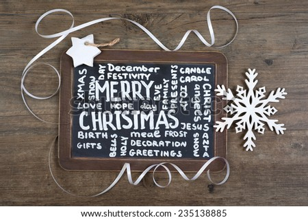 """Black charcoal board with caption """"Merry Christmas"""" and many related words on oak wood  - stock photo"""