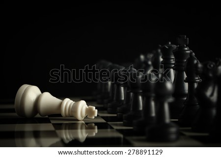 Black chess army defeats white king on the chess board. - stock photo