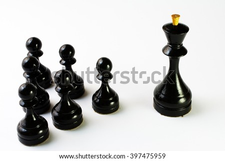 Black chess pawns with king on the white background