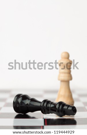 Black chess piece lying while white standing against white background - stock photo