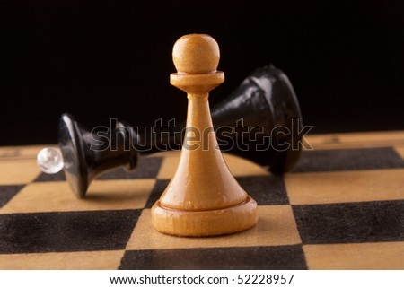 black chess queen lays on a chessboard, black background