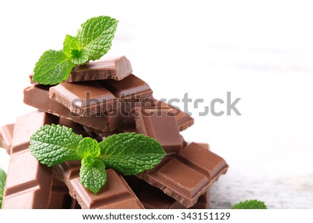 Black chocolate pieces and mint leaves on color wooden background - stock photo