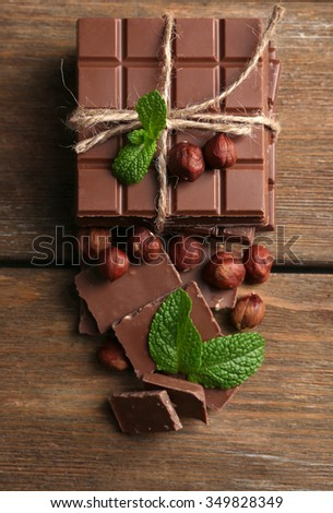 Black chocolate pieces with nuts on wooden background - stock photo