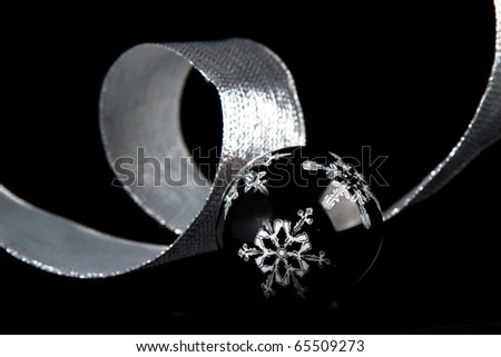 Black christmas ball with the white snowflake on the black background - stock photo