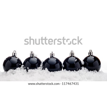Black christmas balls with snow isolated on white background - stock photo