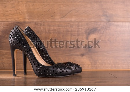 black classic  high heeled refined  black patent leather shoes  on brown parquet  wooden floor with copy place  - stock photo